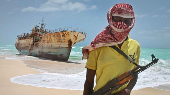 A masked and armed Somali pirate stands near a fishing vessel washed ashore. (AP Photo/Farah Abdi Warsameh)