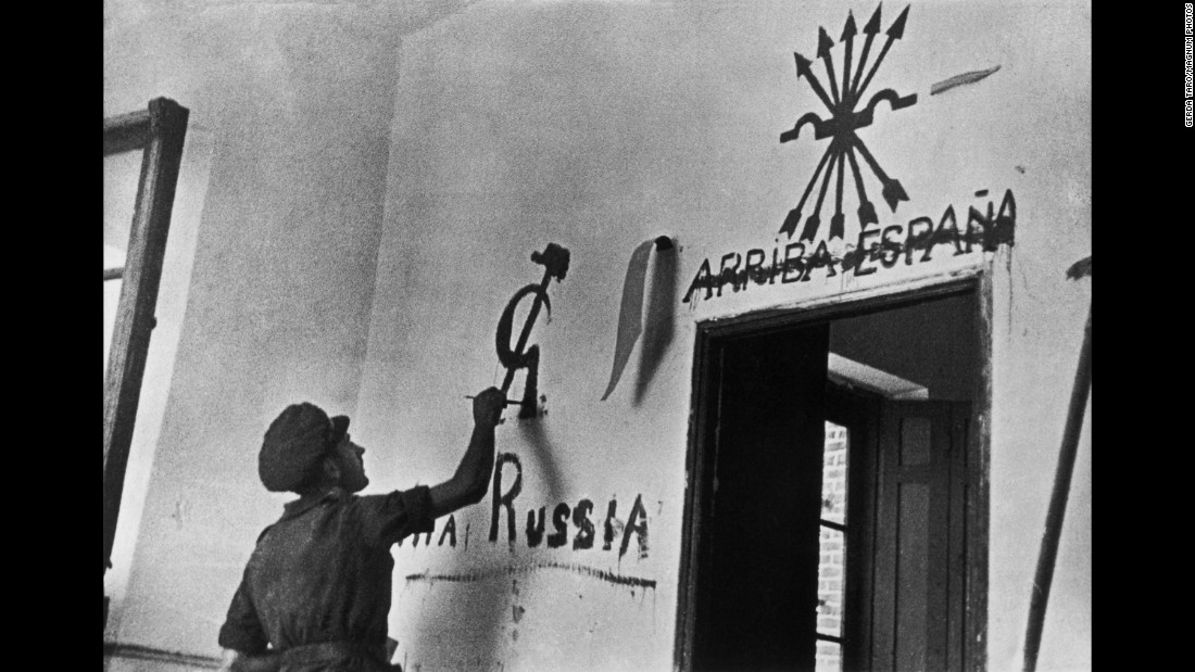 A Republican soldier draws a communist symbol after crossing out a pro-Franco slogan in Aragon.