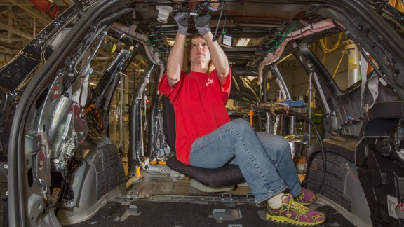 "General Motors assembly team member LeAnn Franke uses the ""Ergo Chair"" while connecting wire harnesses to a 2014 Chevrolet Traverse Wednesday, May 7, 2014 at GM"