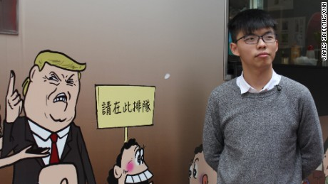 Joshua Wong poses with a mural of US President Donald Trump in Hong Kong's Sheung Wan district.