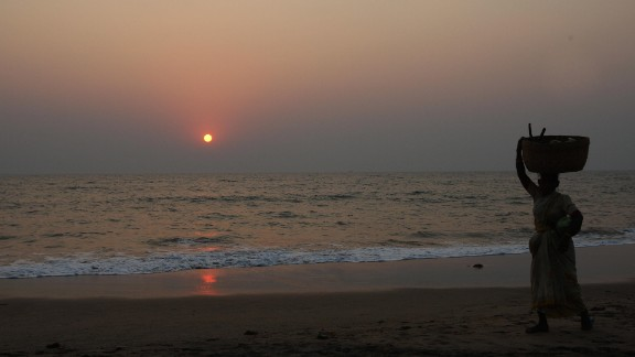 A woman walks on a beach in Goa, an Indian state popular with tourists from around the world.