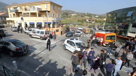 People stand outside a police security cordon near the  Alexis de Tocqueville high school in Grasse on Thursday.