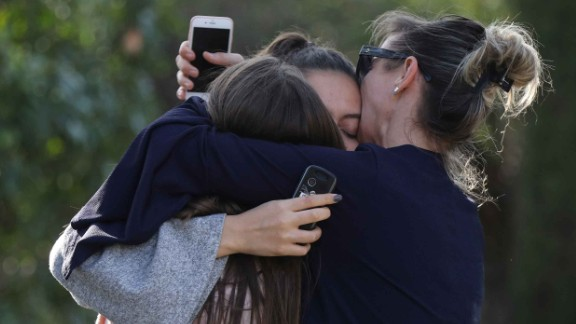 People react near the high school following the shooting.