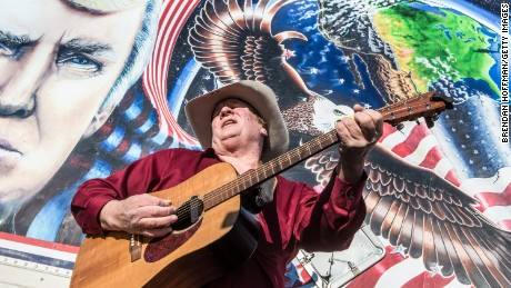 Kraig Moss, a supporter of Donald Trump during the campaign, sings a song outside a truck with a Trump painting last year in Iowa. Now, he regrets doing so.