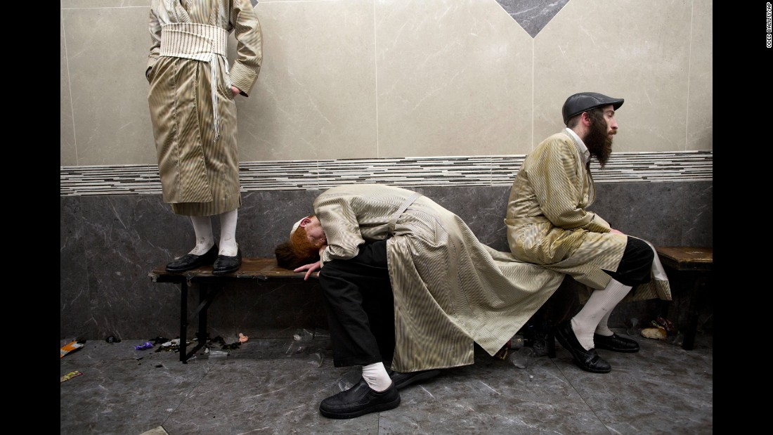 Intoxicated men rest in Jerusalem as they celebrate the Jewish holiday of Purim on Monday, March 13.