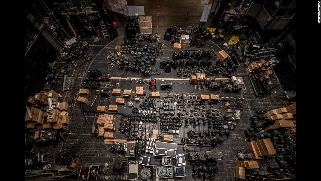 A worker walks between spotlights that were gathered backstage at the State Opera in Prague, Czech Republic, on Sunday, March 13. The building is being reconstructed.