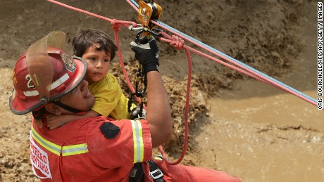 Residents of the Huachipa populous district, east of Lima, are helped on March 17, 2017, by police and firemen rescue teams to cross over flash floods hitting their neighbourhood and isolating its residents. The climatic phenomenon El Niño is causing muddy rivers overflows on the entire Peruvian coast, isolating hundreds of people, mostly residents of Limas industrial belt neighbourhoods. / AFP PHOTO / CRIS BOURONCLE        (Photo credit should read CRIS BOURONCLE/AFP/Getty Images)