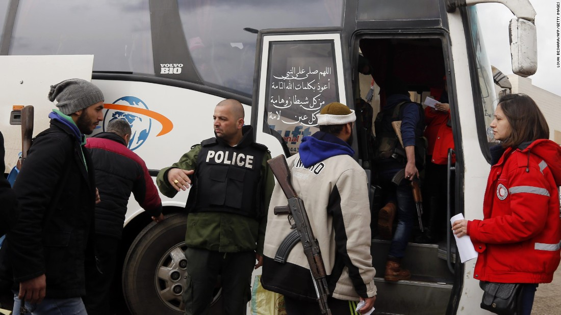 A Russian military police officer instructs opposition fighters and their families as they get on a bus.