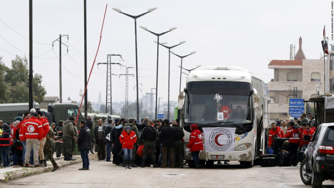 Opposition fighters and their families get on a bus as part of their evacuation from the rebel-held Al-Waer neighborhood in the central city of Homs on Saturday.