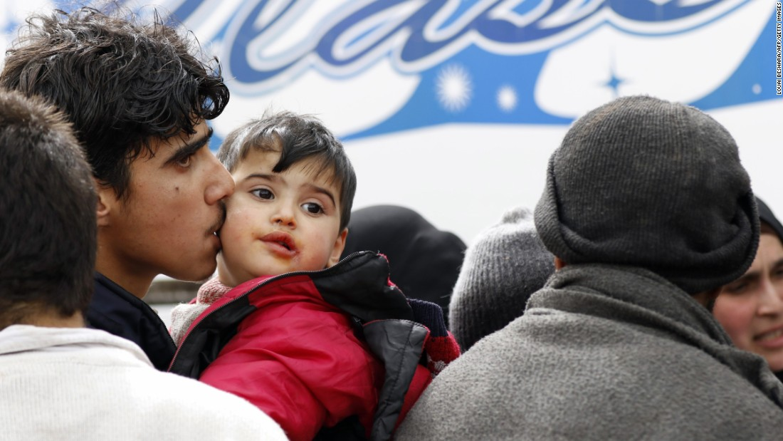 A man kisses his child as they prepare to get on a bus.