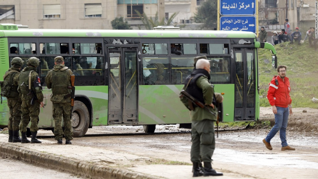 Members of the Russian military police and Syrian regime soldiers stand guard as a bus drives by.
