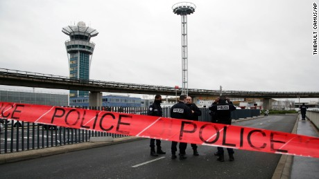 Police officers cordon off the access to the Orly airport, south of Paris, Saturday, March, 18, 2017. A man was shot to death Saturday after trying to seize the weapon of a soldier guarding Paris' Orly Airport, prompting a partial evacuation of the terminal, police said. Authorities warned visitors to avoid the area while an ongoing police operation was underway.