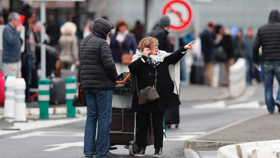 A woman talks on her cell phone as travelers evacuate Paris