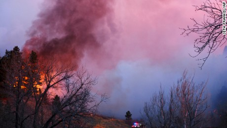 Smoke rises from a wildfire Sunday, March 19, 2017, in Boulder, Colorado. Authorities said the small wildfire burning in the mountains forced people from their homes and is filling the sky with smoke.