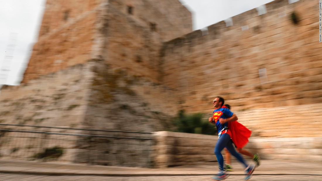 A competitor dressed as Superman runs along the Old City ramparts.
