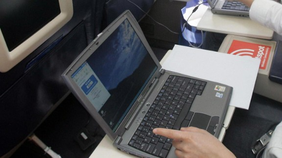 """BEIJING, CHINA:  Guests try out the wireless connection to the Internet on their laptops onboard US aerospace giant Boeing's latest aircraft """"Connexion"""", which allows passengers to connect on the Internet wireless while flying, at the Beijing Capital airport 21 September 2005.  Boeing claimed that China will need more than 2,600 new planes worth 213 billion USD over the next 20 years, quadrupling its fleet to become the world's second largest aviation market.           AFP PHOTO  (Photo credit should read STR/AFP/Getty Images)"""
