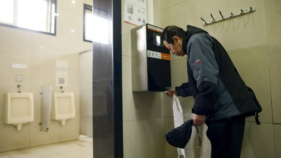 A man uses an automatic toilet paper dispenser that uses facial recognition technology at a public toilet at the Temple of Heaven in Beijing on March 21, 2017.  A years-long crime spree by Chinese toilet paper thieves may have reached the end of its roll after park officials in southern Beijing installed facial recognition technology to flush out bathroom bandits. / AFP PHOTO / WANG Zhao        (Photo credit should read WANG ZHAO/AFP/Getty Images)