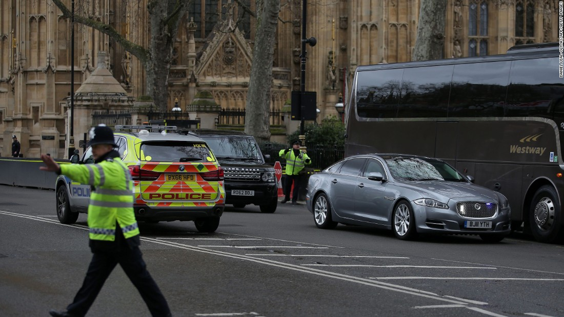 At right, the car of British Prime Minister Theresa May is driven away from Parliament.