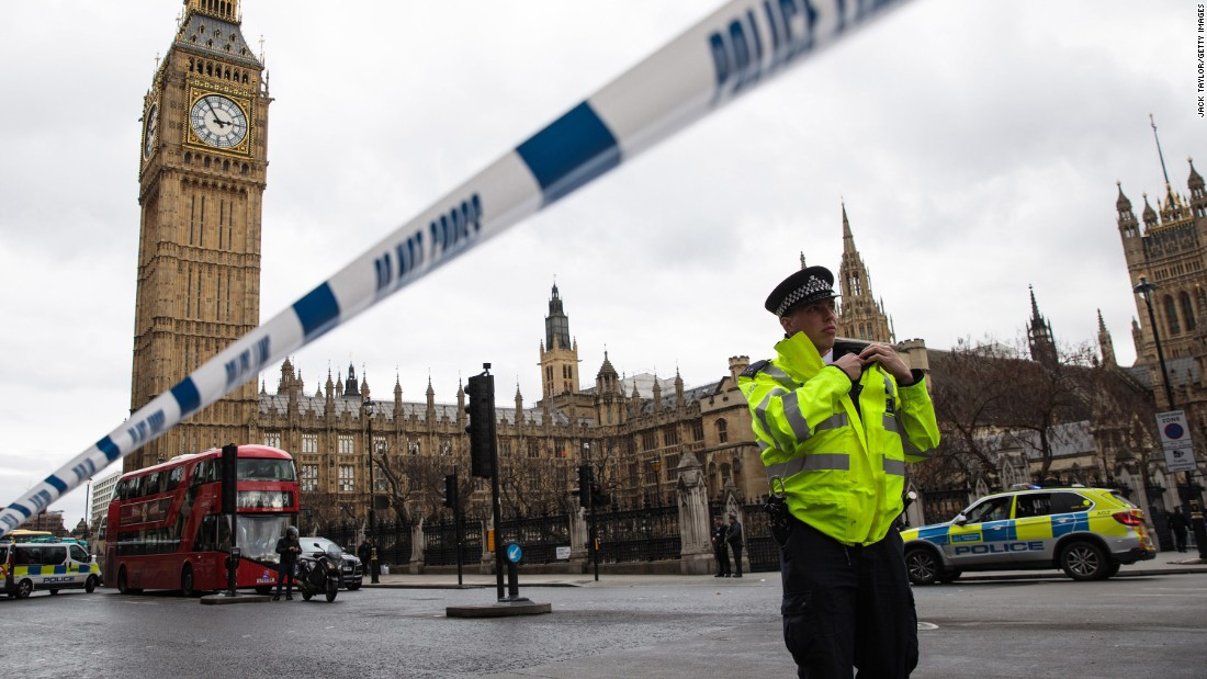 A police officer stands guard near Westminster Bridge and the Houses of Parliament.