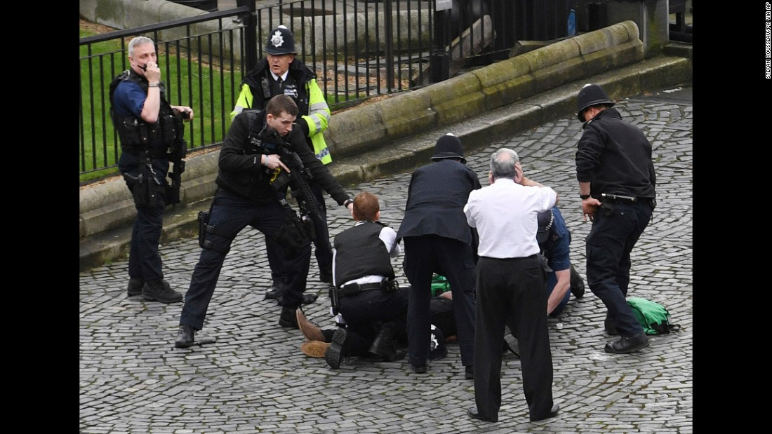 "An armed police officer stands over the attacker, identified as Khalid Masood, outside Parliament. ""It appeared that a car was coming towards the House of Commons mowing down pedestrians on the way,"" Member of Parliament Gerald Howarth told CNN. ""The driver then got access to the parliamentary estate, stabbed a police officer and was shot."""