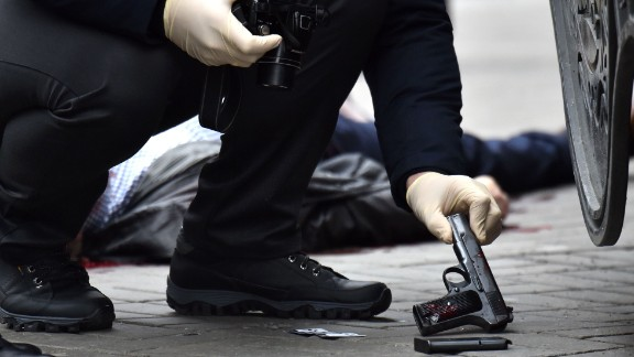A Ukrainian police officer seizes a gun at the scene where Voronenkov was shot dead on Thursday.