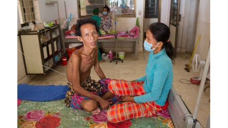 Meas Mao, 48, sits next to her husband on the TB ward at Kampong Cham District Hospital. He has TB meningitis.