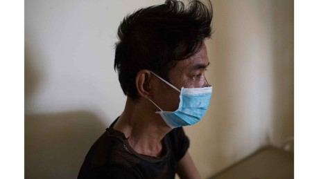 Ly Meng, 48, sits in his room on the drug-resistant TB ward at CENAT hospital in Phnom Penh. He is co-infected with HIV and drug-resistant TB.
