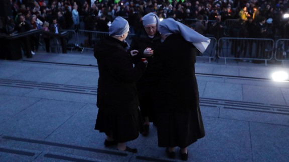 A group of nuns light candles during the Trafalgar Square event.