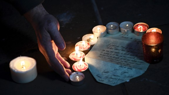 A letter is left among votive candles during the vigil.