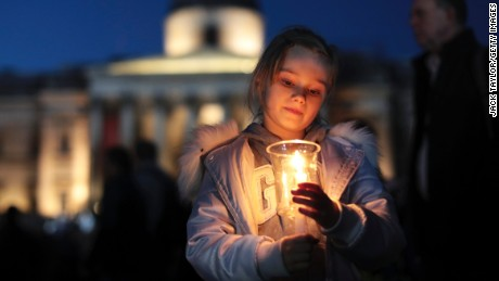 A young girl lights a candle during a candlelit vigil at Trafalgar Square on March 23, 2017 in London, England.
