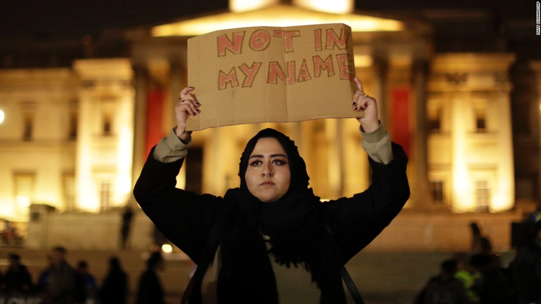 A woman wearing traditional Muslim dress holds up a sign at the vigil.