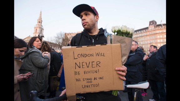 """Patrick Johnson holds a sign that reads, """"London will never be beaten! We stand as one and united!"""" Johnson says his mother was caught up in the 7/7 bombings in 2005, the coordinated attacks on London's transport system that left 52 dead and more than 700 injured. """"This isn't going to defeat anyone,"""" he said in a thick east London accent. """"We're strong."""" """"7/7, that didn't break us. This won't either."""""""