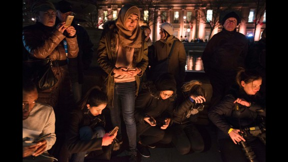 """Friends Aklima Ahmed, 19, (bottom left), Lipa Nessa, 18, (center, standing), and Aklima Ahmed, 19, participate in the vigil. Nessa told CNN that """"as a Muslim, I felt I had to come here to show that nothing can divide us, that we are united together, to make London stronger."""""""
