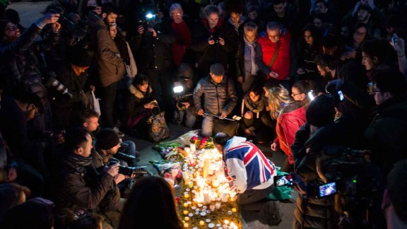 The crowd huddles around 62-year-old John Loughrey (center, draped in Union Jack flag) as he lights candles in tribute to the victims.