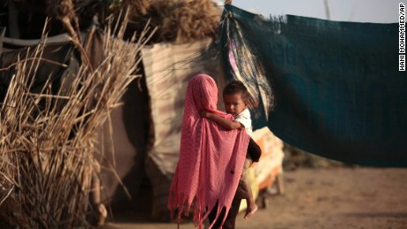 A displaced girl holds her brother at a camp for internally displaced people near the town of Abs, located on Yemen's western coastal plain.