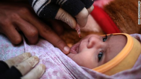 An infant receives a polio vaccination during a house-to-house polio immunization campaign in Sanaa.