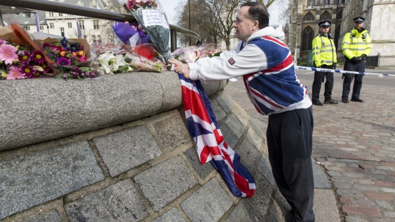 A man places a floral tribute near a police cordon in Westminster in central London on March 23, 2017 a day after a deadly terror attack killed at least three people.  Britain's parliament reopened on Thursday with a minute's silence in a gesture of defiance a day after an attacker sowed terror in the heart of Westminster, killing three people before being shot dead. Sombre-looking lawmakers in a packed House of Commons chamber bowed their heads and police officers also marked the silence standing outside the headquarters of London's Metropolitan Police nearby.  / AFP PHOTO / Joel Ford        (Photo credit should read JOEL FORD/AFP/Getty Images)