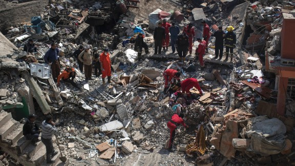 Civil protection rescue teams comb through the debris of a destroyed house to recover the bodies of people killed during fights between Iraq security forces and the Islamic State on the western side of Mosul.
