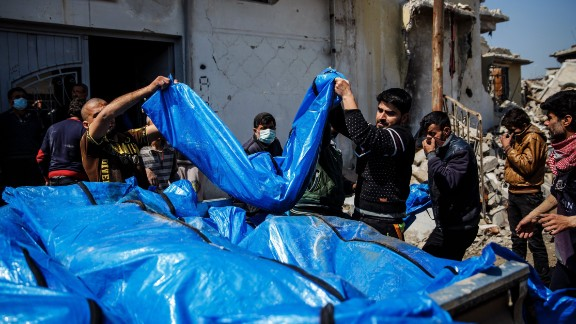 Residents pile body bags into the back of a pickup truck after recovering them from the rubble in the al Jadidah neighborhood of Mosul.