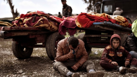 Relatives mourn as bodies of Iraqis killed in a Mosul airstrike are placed on carts on March 17.