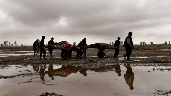Residents of Mosul, Iraq, remove the bodies of Iraqis who were killed in an airstrike targeting the Islamic State (ISIS) on March 17, 2017. Iraq is investigating airstrikes in west Mosul that reportedly killed large numbers of civilians in recent days, a military spokesman said.