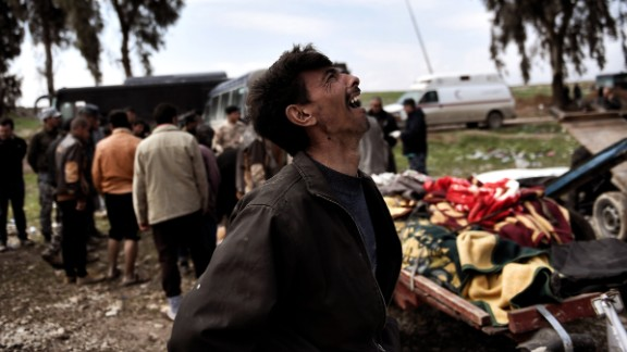 A man mourns near the bodies of Iraqi residents killed in a March 17 airstrike in Mosul.