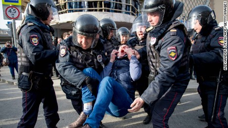 Riot police officers detain a protester during an unauthorised anti-corruption rally in central Moscow on March 26.