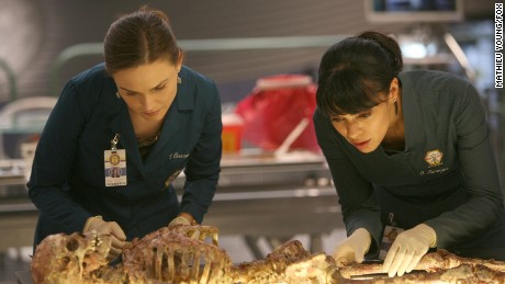 "Brennan (Emily Deschanel, L) and Cam (Tamara Taylor, R) examine the remains of a young boy who could help them convict the Gravedigger in the 'Bones' episode ""The Boy with the Answer."""