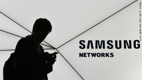 A visitor uses his mobile phone as he walks past the stand of Samsung on the second day of the Mobile World Congress in Barcelonaon on February 28, 2017. Phone makers will seek to seduce new buyers with artificial intelligence functions and other innovations at the world's biggest mobile fair starting today in Spain.   / AFP / LLUIS GENE        (Photo credit should read LLUIS GENE/AFP/Getty Images)