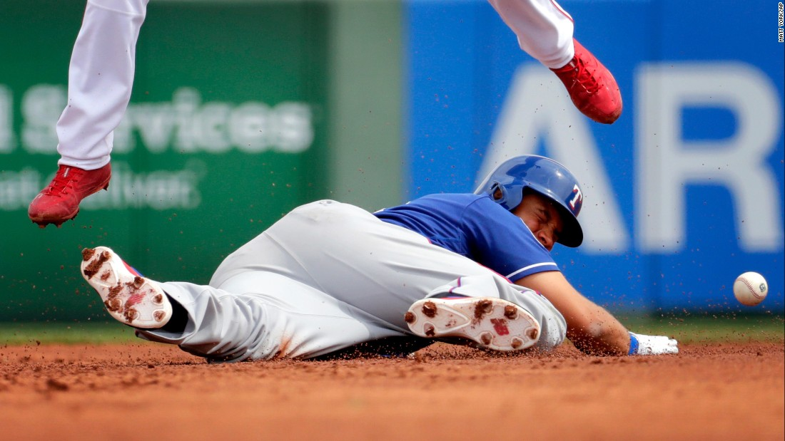 Texas Rangers' James Loney is hit by the ball while diving back to second base as Los Angeles Angels' Andrelton Simmons leaps out of the way during a spring training game, on Wednesday, March 22.