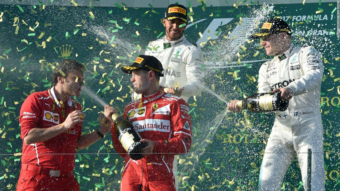 Ferrari German driver Sebastian Vettel sprays champagne at trackside engineering team member Luigi Fraboni as he celebrates his victory with runner-up Mercedes' British driver Lewis Hamilton, back left, and third-place Mercedes' Finnish driver Valtteri Bottas at the end of the Australian Grand Prix in Melbourne on Sunday, March 26.