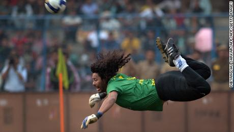 Former Colombian goolkeeper Rene Higuita kicks the ball to save a goal during an exhibition match between the Brazilian Masters and Indian All Stars in Kolkata on December 8, 2012. The Brazilian team won the match by 3-1. AFP PHOTO/ Dibyangshu SARKAR        (Photo credit should read DIBYANGSHU SARKAR/AFP/Getty Images)