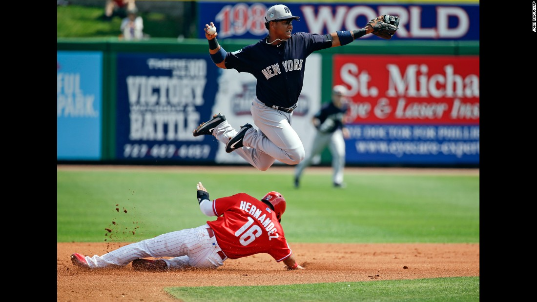 New York Yankees second baseman Starlin Castro throws to first base as he leaps over Philadelphia Phillies' Cesar Hernandez in the first inning of a spring training game on Wednesday, March 22.