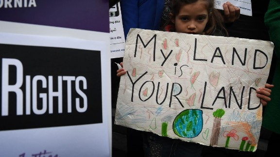 "Maya Casillas, 7, joins migrant rights group during a vigil to protest against President Donald Trump's new crackdown on ""sanctuary cities"", outside the City Hall in Los Angeles on January 25, 2017."